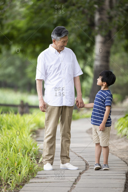 Happy Chinese grandfather and grandson holding hands in park