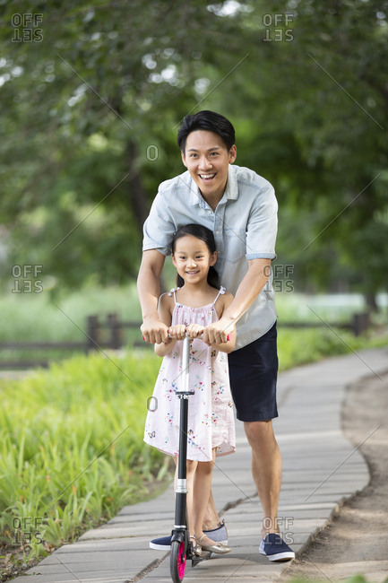 Happy Chinese father and daughter riding push scooter in park