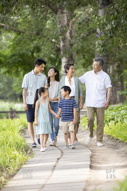 Happy Chinese family walking in park