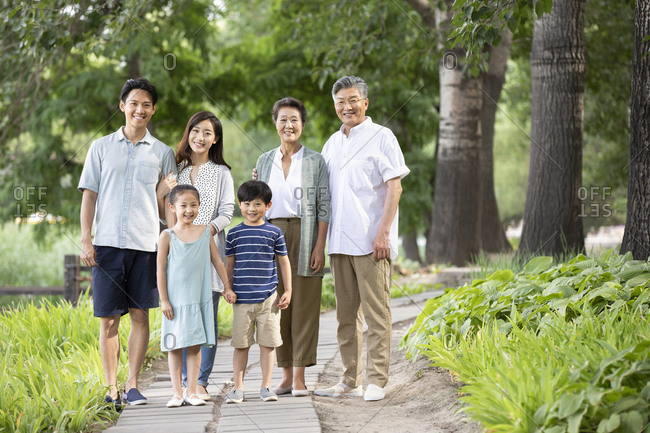 Happy Chinese family relaxing in park
