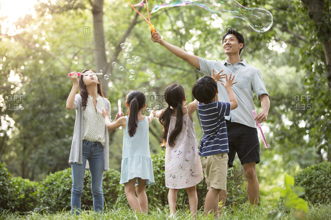 Happy young Chinese family blowing bubbles on grass