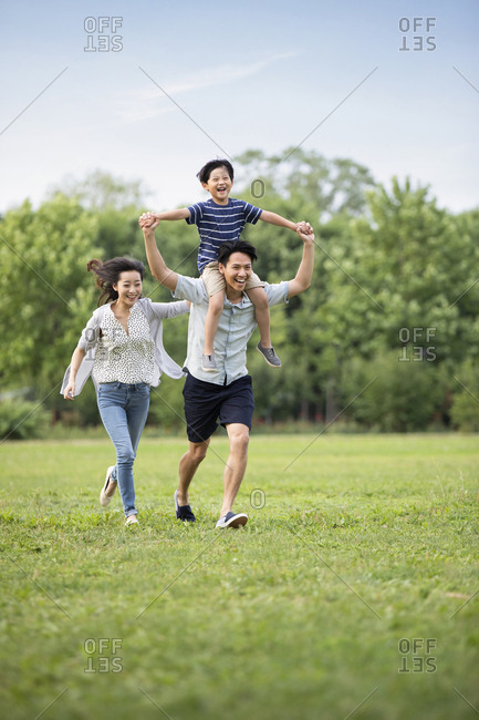 Happy young Chinese family playing on grass