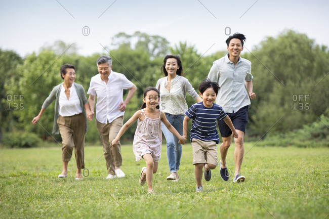 Happy Chinese family running on grass