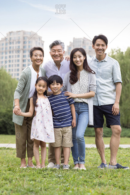 Happy Chinese family standing on grass