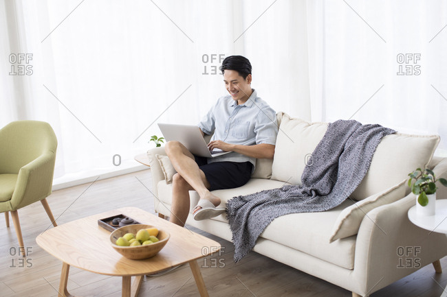 Happy young Chinese man using laptop in living room