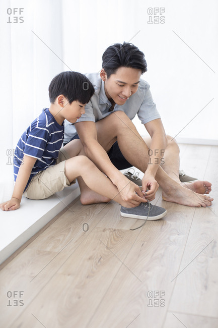 Chinese father teaching his son to tie shoelaces