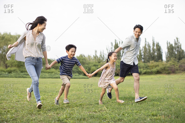 Happy young Chinese family running on grass