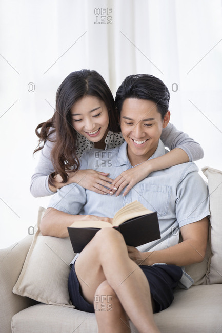 Happy young Chinese couple reading book in living room