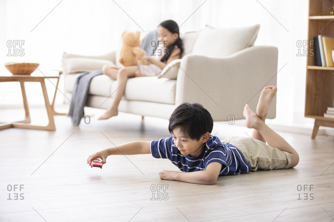 Happy Chinese sibling playing with toys in living room