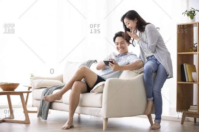Happy young Chinese couple using smartphone in living room