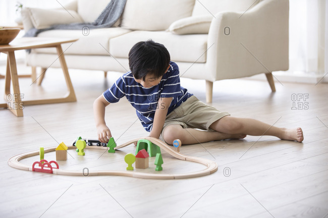 Little Chinese boy playing with toy train on floor