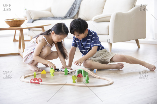 Happy Chinese sibling playing with toy train on floor