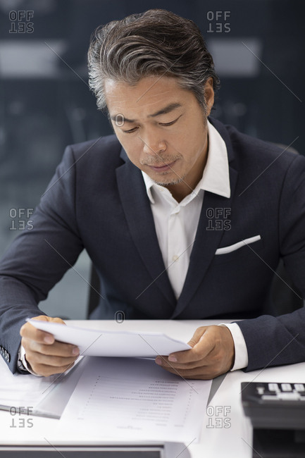 Successful Chinese businessman reading documents in office