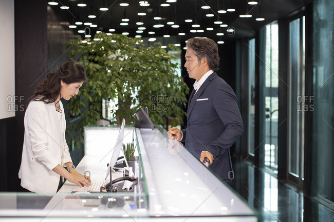 Chinese receptionist dealing with businessman