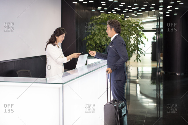 Mature Chinese businessman giving business card to receptionist