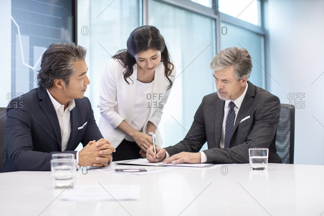 Business people signing contract in conference room