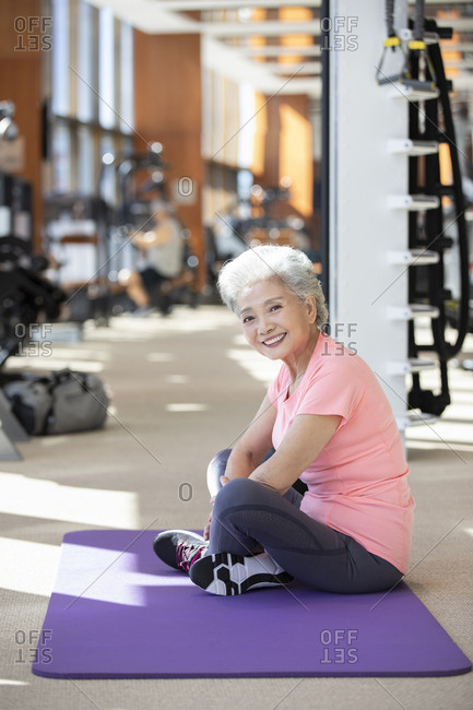 Senior Chinese woman sitting on exercise mat at gym