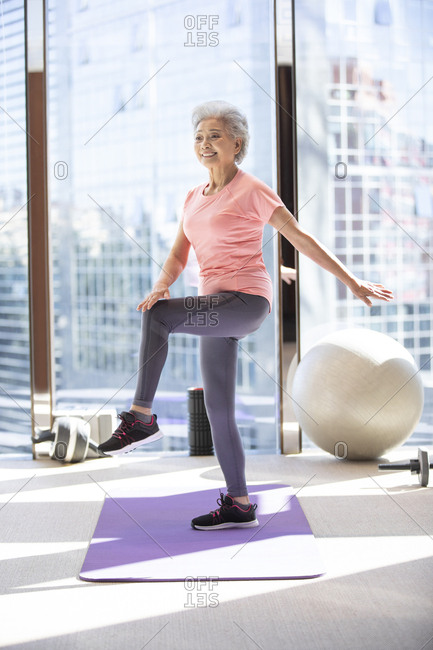 Senior Chinese woman exercising at gym