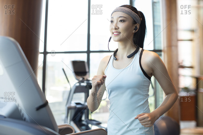 Young Chinese woman running with wireless headphone at gym