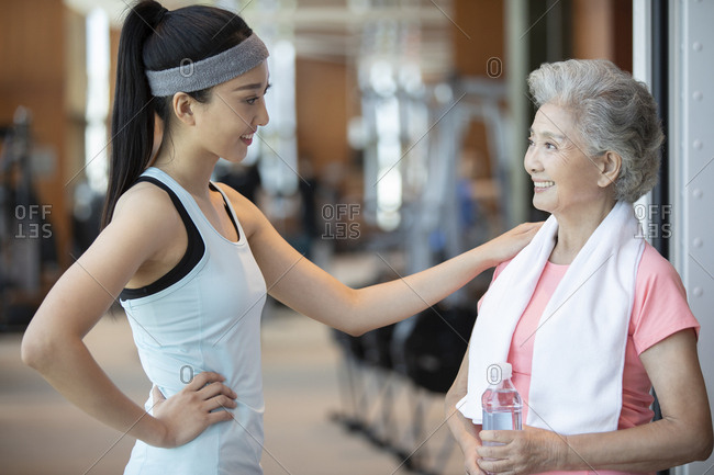 Senior Chinese woman taking a break after exercising at gym