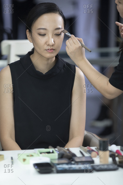 Chinese makeup artist applying makeup on model