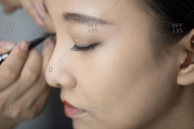 Chinese makeup artist applying makeup on model