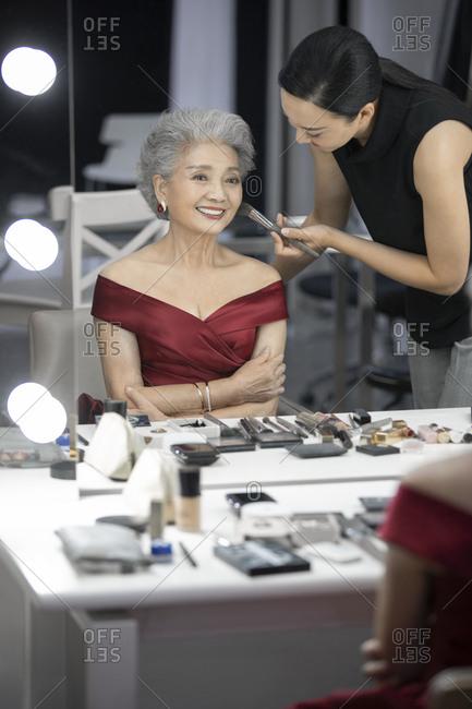 Chinese makeup artist applying makeup on senior woman