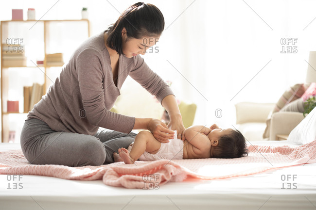 Young Chinese mom changing her baby girl's diaper