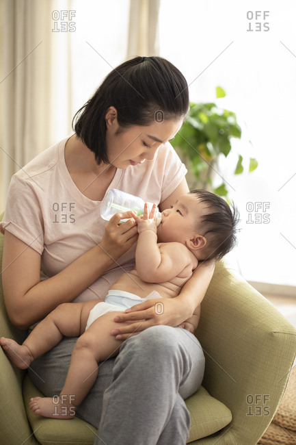 Young Chinese mom feeding baby girl with bottle