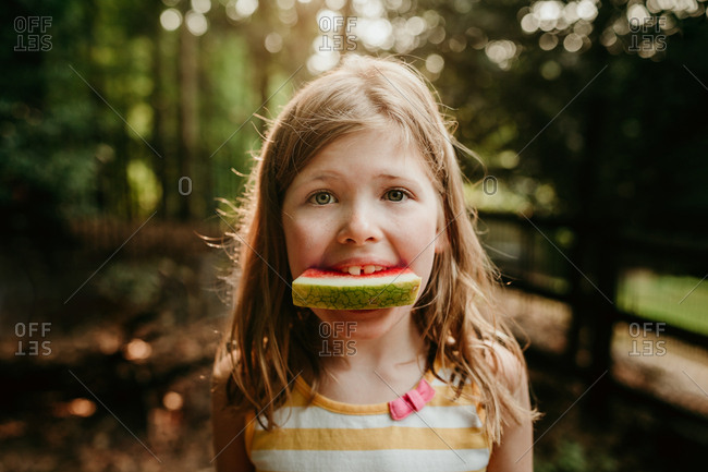 Close up of a girl eating watermelon in the forest