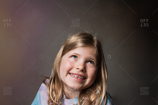 Portrait of a little blonde girl with braces
