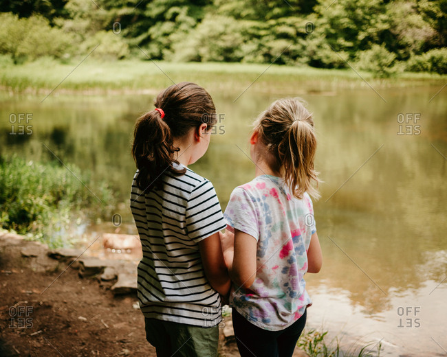 Two little girls standing by a lake