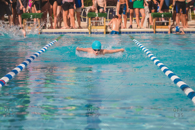 Boy wearing blue swim cap racing at a swim meet