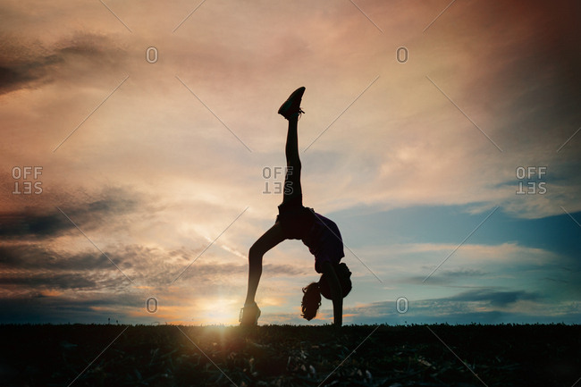 Silhouette of a girl doing a back bend at sunset