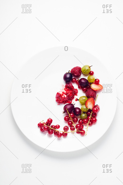 Overhead composition with various berries on white ceramic plate