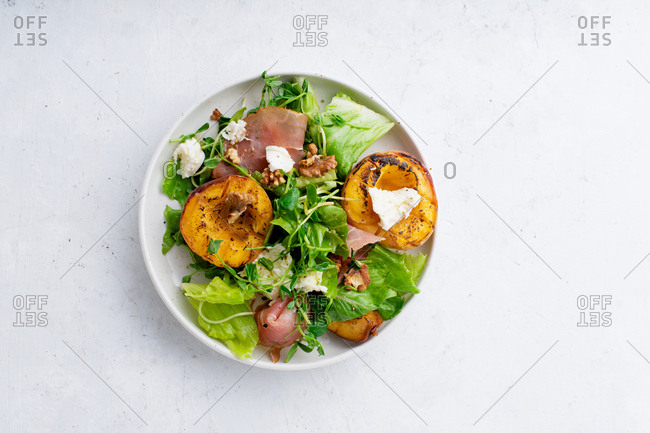 Top view image of grilled peach and mozzarella salad with prosciutto