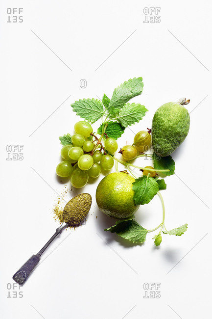 Flatlay composition with melissa leaves, feijoa, gooseberries and lime