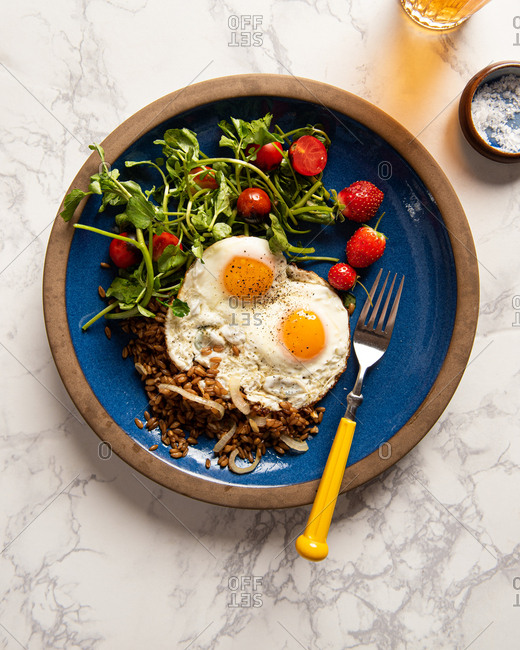 Two sunny side up eggs on a plate with salad