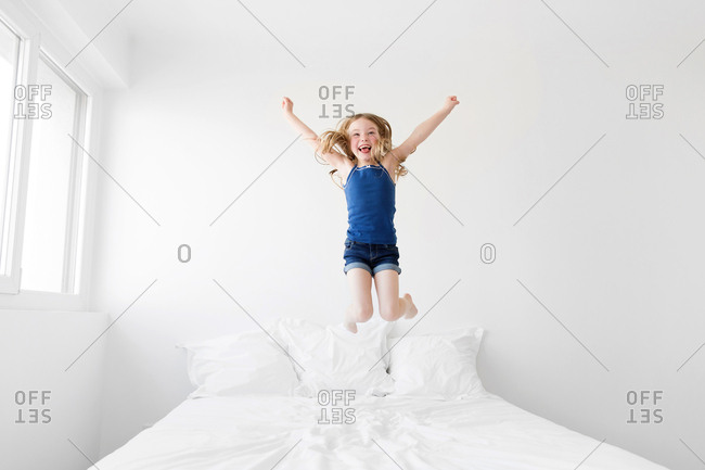 Young girl jumping with joy on white bed