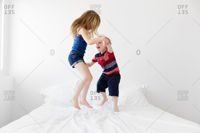 Brother and sister dancing on bed holding hands