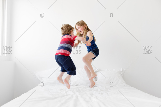 Brother and sister jumping and dancing on bed together