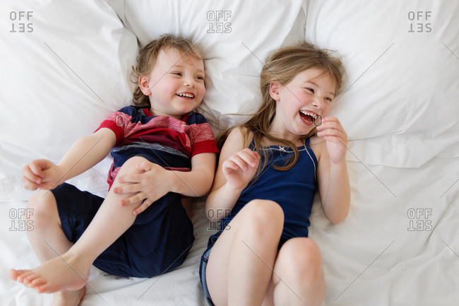 Brother and sister lying on bed laughing together