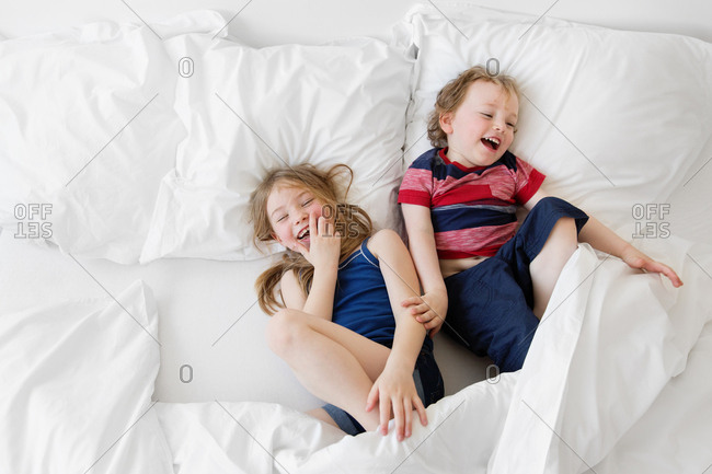 Siblings lying on white bed laughing together