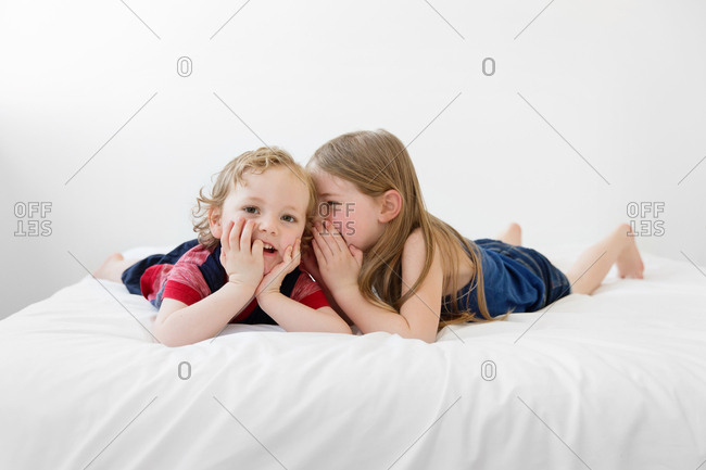 little girl whispering secrets to her brother