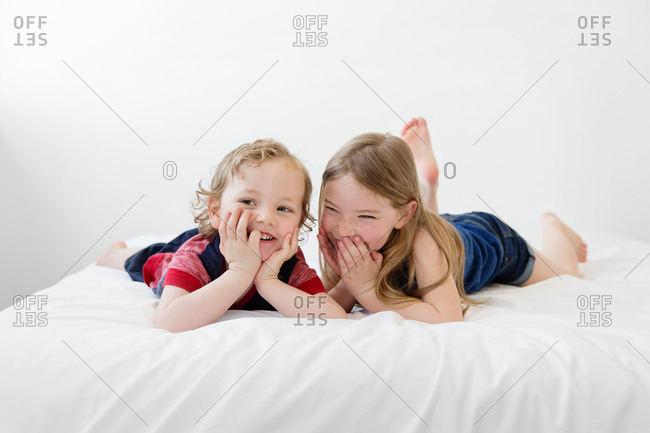Brother and sister giggling together on white bed