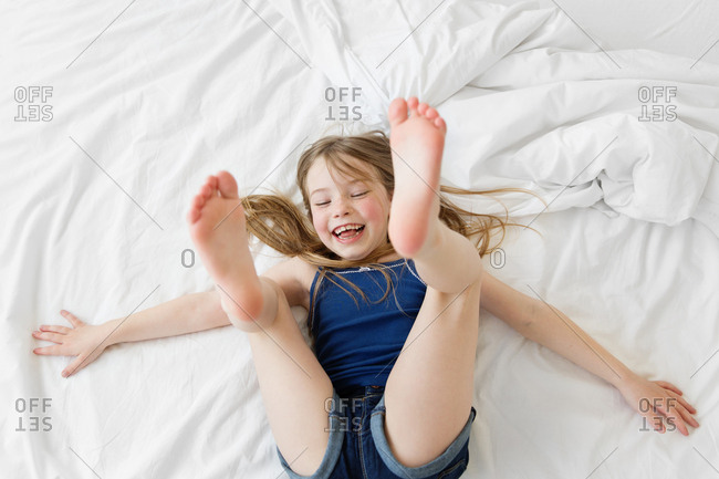 Laughing young girl bouncing on her back on a bed
