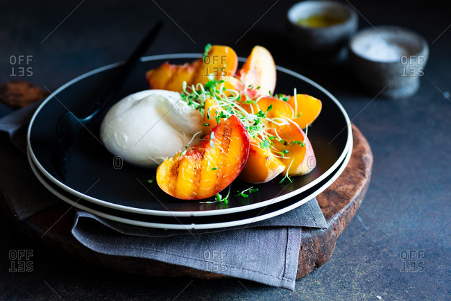 Burrata cheese with grilled peaches and microgreens on black plate