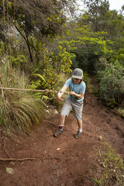 Boy climbing steep, slippery path with rope, Kauai