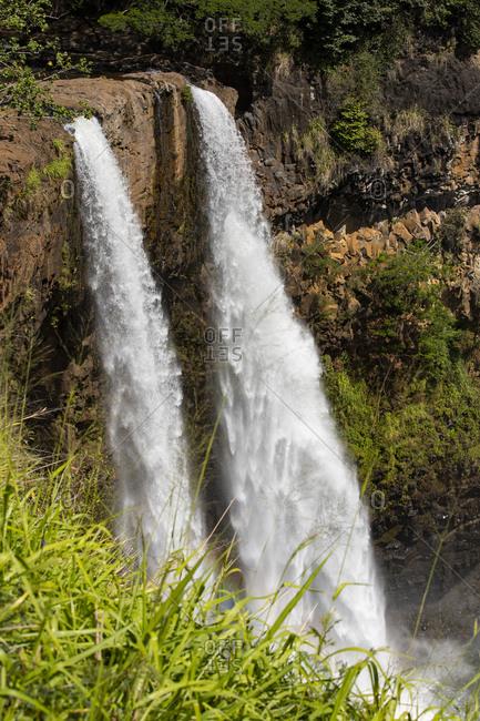 Wailua falls drop over cliff edge, Kauai