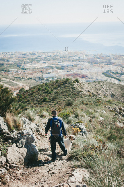 Man hiking down a hill with dog overlooking city and ocean in malaga